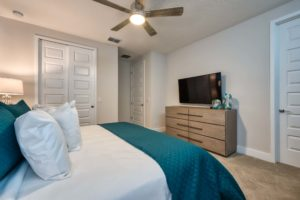 Large king bed, wall-mounted TV, and wide dresser in an Eagle Trace resort residence.
