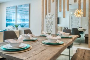 Dining room in an Eagle Trace resort residence featuring modern wall art, decorations, and a wood finish table set for a meal.