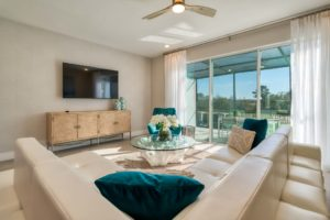 Spacious living room with plush sitting area on either side of a long couch in an Eagle Trace resort residence.